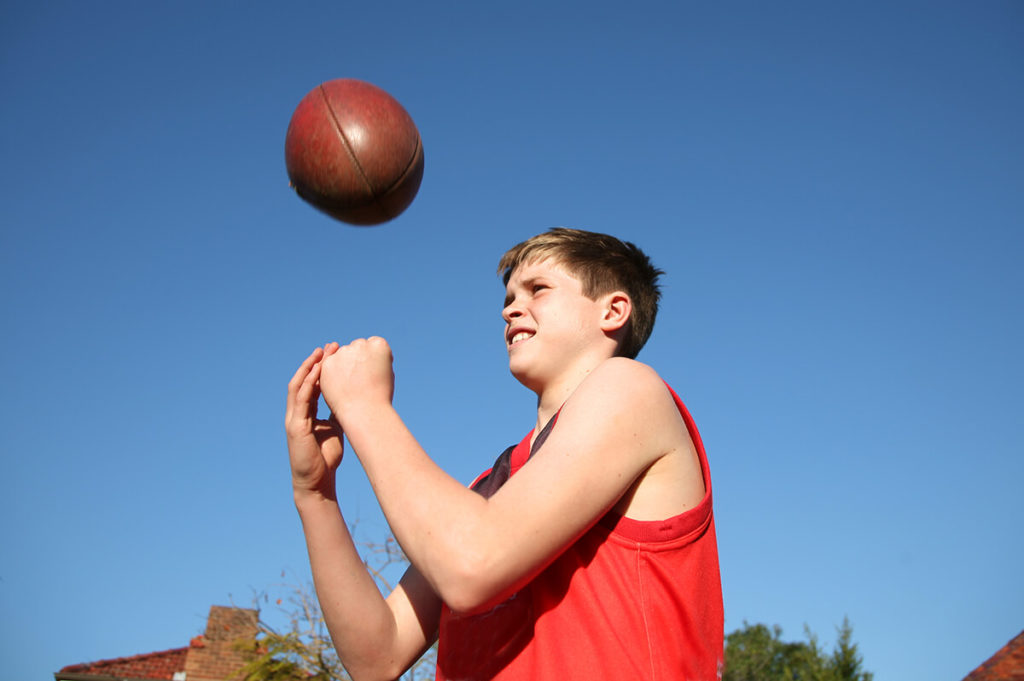 You boy playing with an Australian Rules football